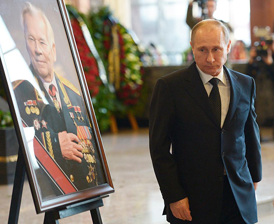 Presiden Rusia Vladimir Putin berjalan melewati sebuah potret perancang senjata api Rusia Mikhail Kalashnikov