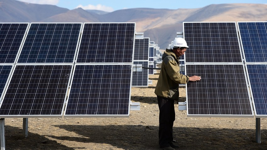 Strokovnjak za sončno energijo si ogleduje celice elektrarne Koš-Agačskaja v Republiki Altaj.