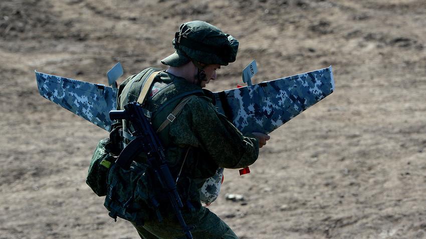 Seorang tentara Rusia bersiap-siap menerbangkan sebuah drone.
