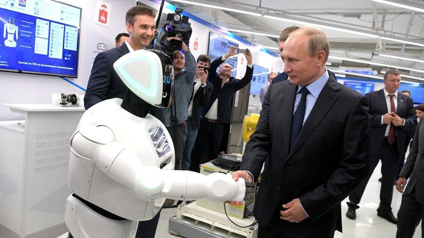 Putin menjabat tangan Promobot yang menyapanya.