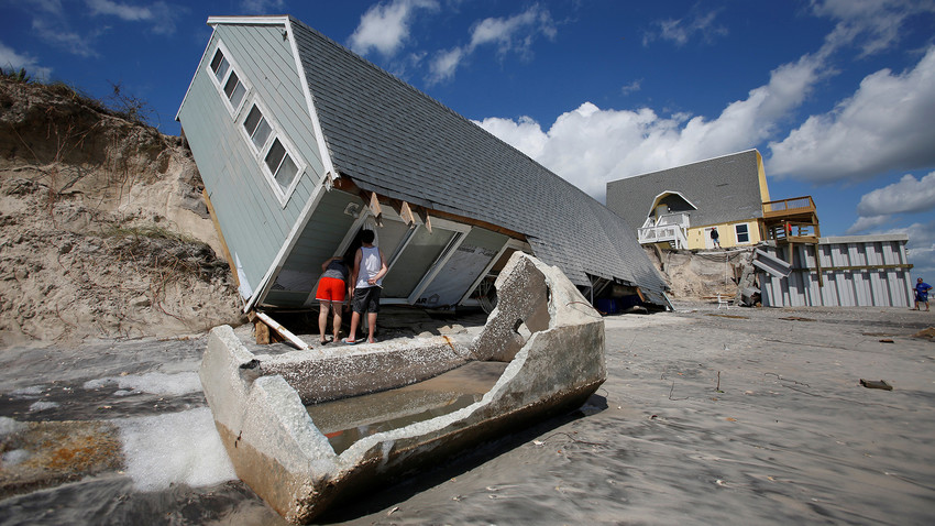 Local residents look inside a collapsed coastal house after Hurricane Irma passed the area in Vilano Beach, Florida, U.S., September 12, 2017.