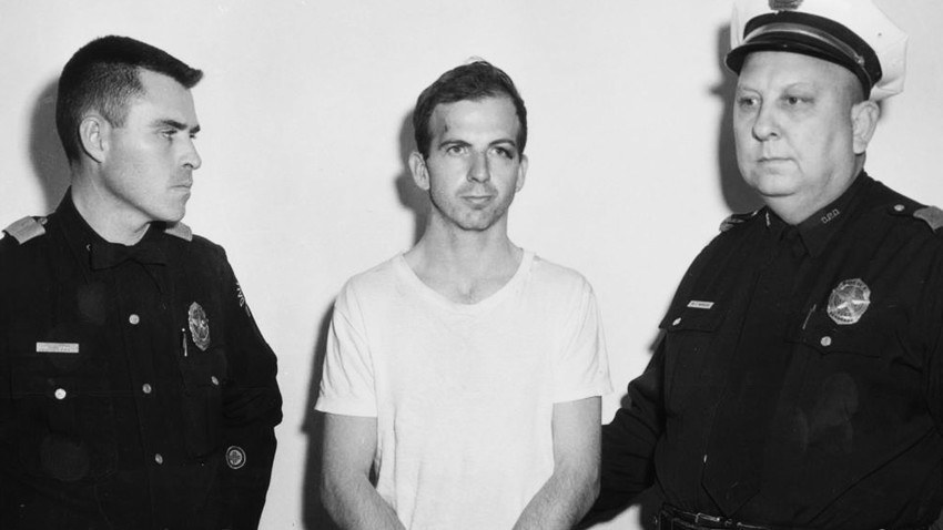 Lee Harvey Oswald, accused of assassinating former U.S. President John F. Kennedy, is pictured with Dallas police Sgt. Warren (R) and a fellow officer in Dallas.