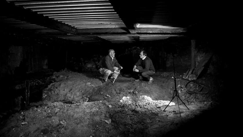 Para pekerja menggali ke bawah bagian tertua di Moskow, dengan memasukkan tanah galian ke kantong sampah pada malam hari
