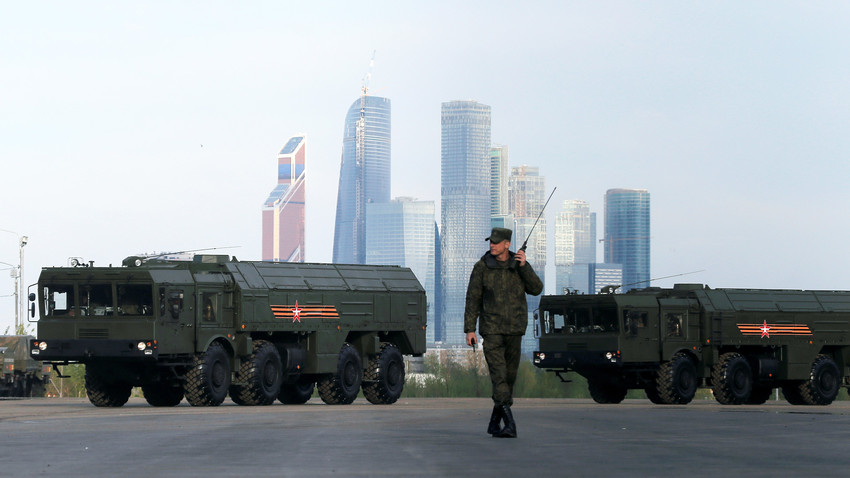 """A Russian serviceman walks past Russian Iskander-M missile launchers with the Moscow International Business Center also known as """"Moskva-City"""" seen in the background, at a range in Moscow, Russia."""