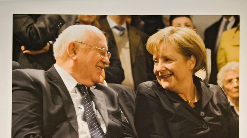 Der ehemalige sowjetische Präsident Michail Gorbatschow und die deutsche Bundeskanzlerin Angela Merkel unterhalten sich unter einem großen Fotodruck im Kennedy-Museum am Pariser Platz in Berlin im Februar 2011.