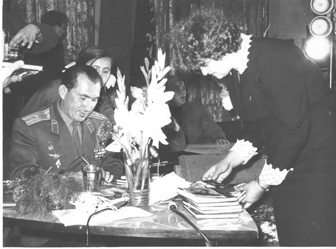 Cosmonauta Pável Beliáev dando autógrafos a jovens. Beliáev foi o primeiro comandante do corpo de cosmonautas e o responsável pela missão Voskhod 2, quando Leonov realizou a primeira caminhada humana no espaço, em 1965.