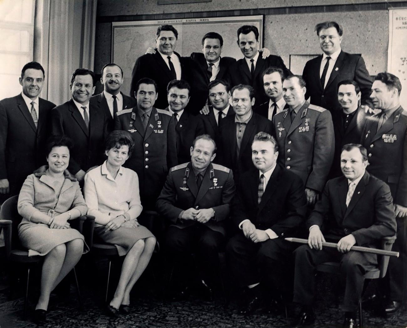 """""""Lápis de Gagárin"""". Gagárin sentado segurando um grande lápis (com os dizeres gravados: 'Feliz Ano Novo 1967'); Andrian Nikolaiev é o quarto a partir da esquerda na segunda fila."""