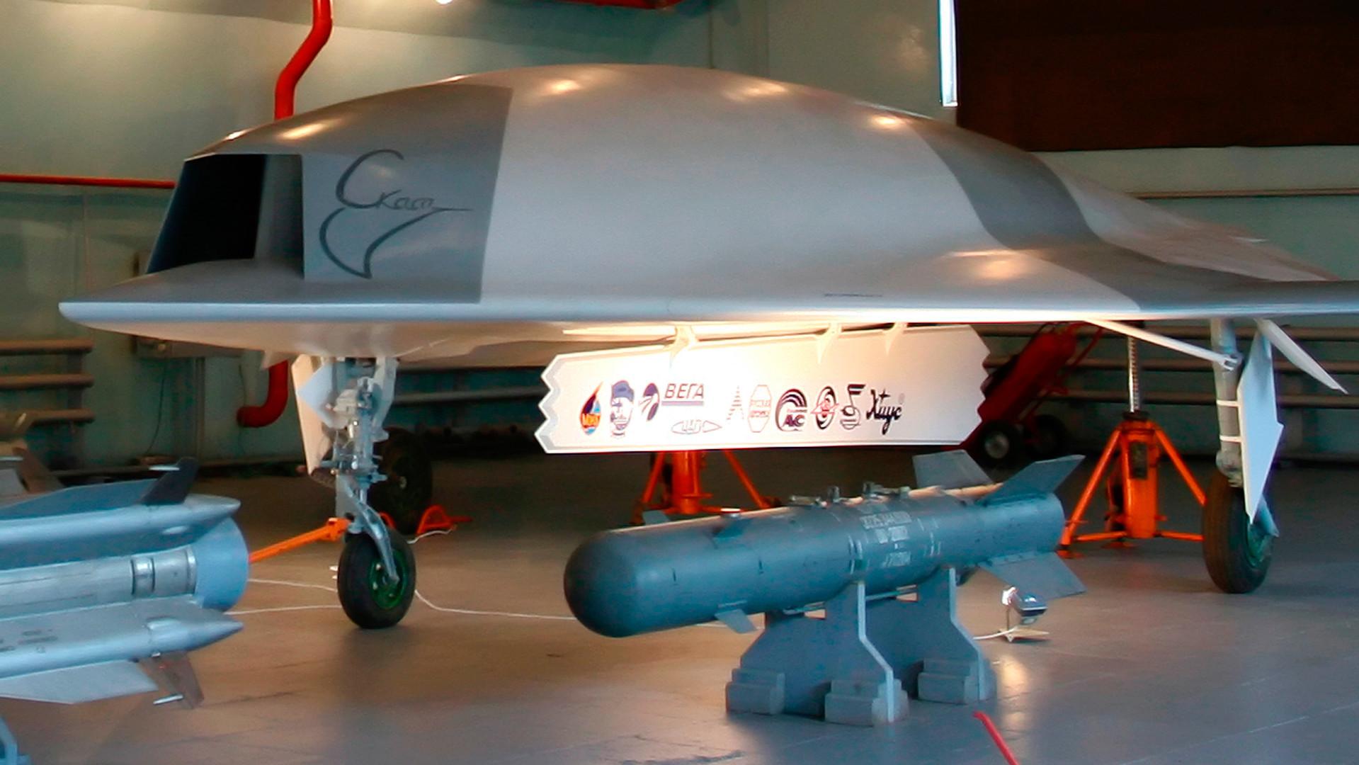 Modelo em tamanho real do veículo aéreo não tripulado Skat (ao fundo) e bombas aéreas (em primeiro plano) em um hangar da fábrica de aeronaves MiG