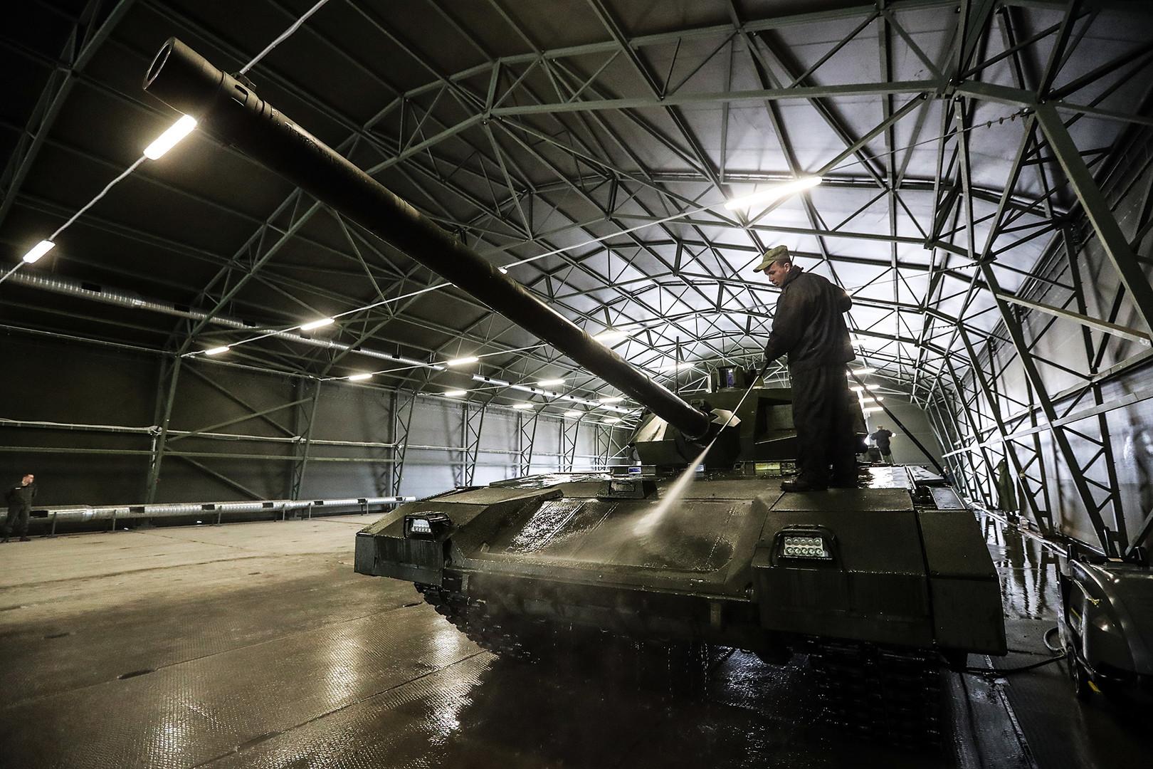 Seorang petugas membersihkan tank T-14 Armata di Moskow.