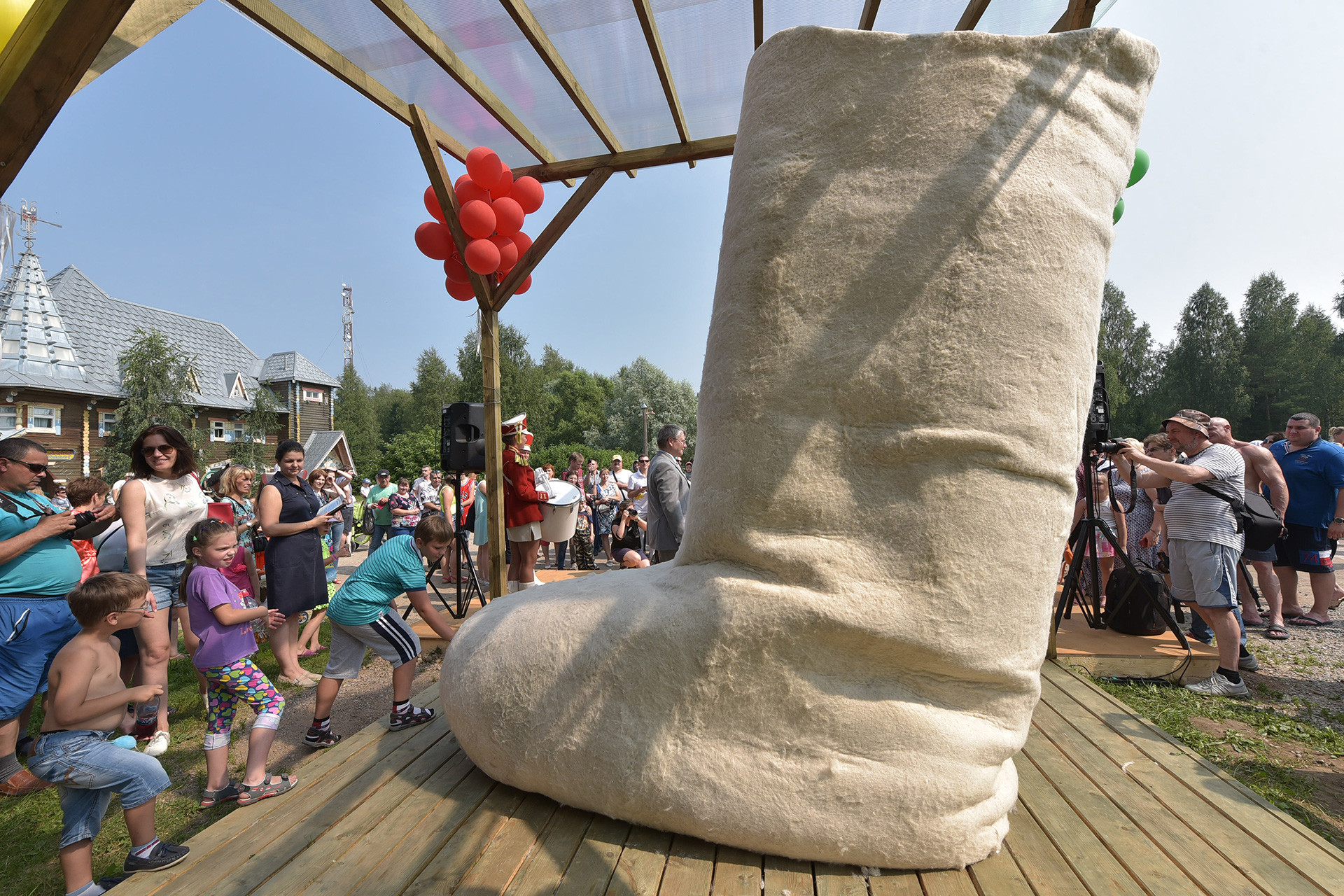 People look at a giant valenki boot made by artist Valeria Loshak