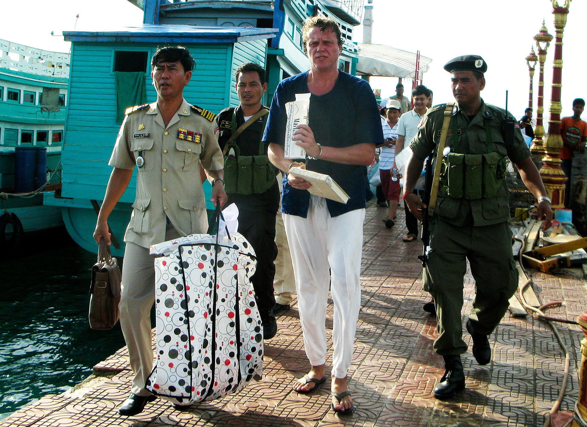 Polonski escoltado por policiais no Camboja