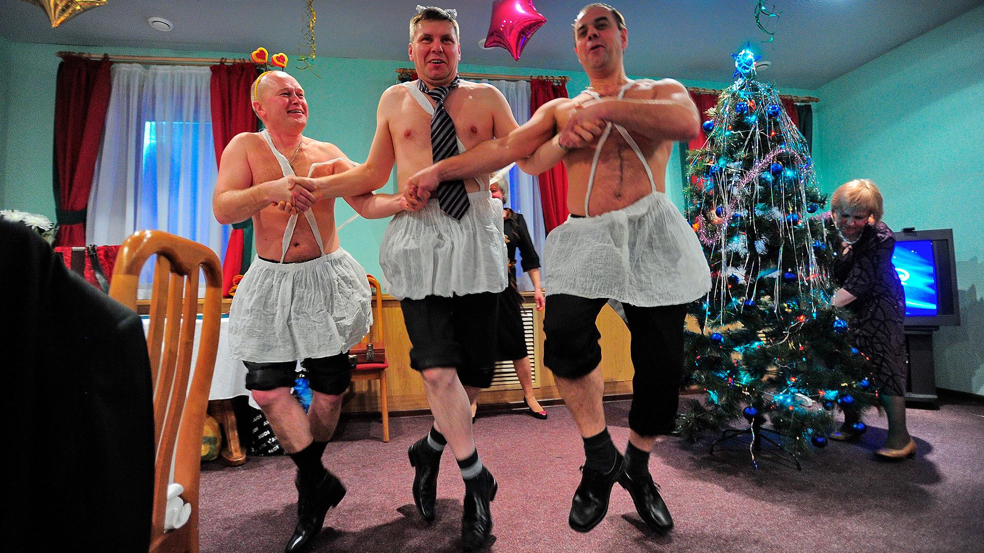 Tiga orang pria tanpa busana berdansa di pesta Natal perusahaan.