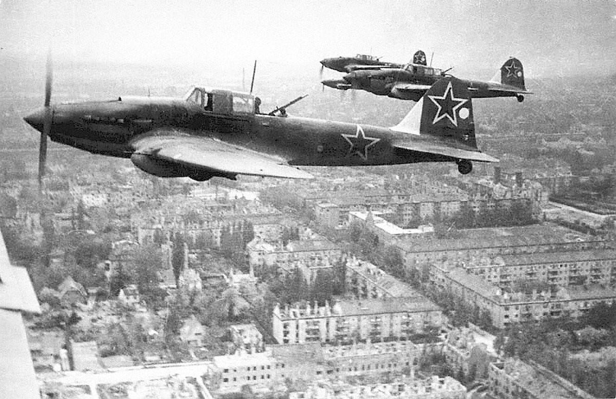Aparatos Il-2 en formación sobrevuelan una ciudad alemana.