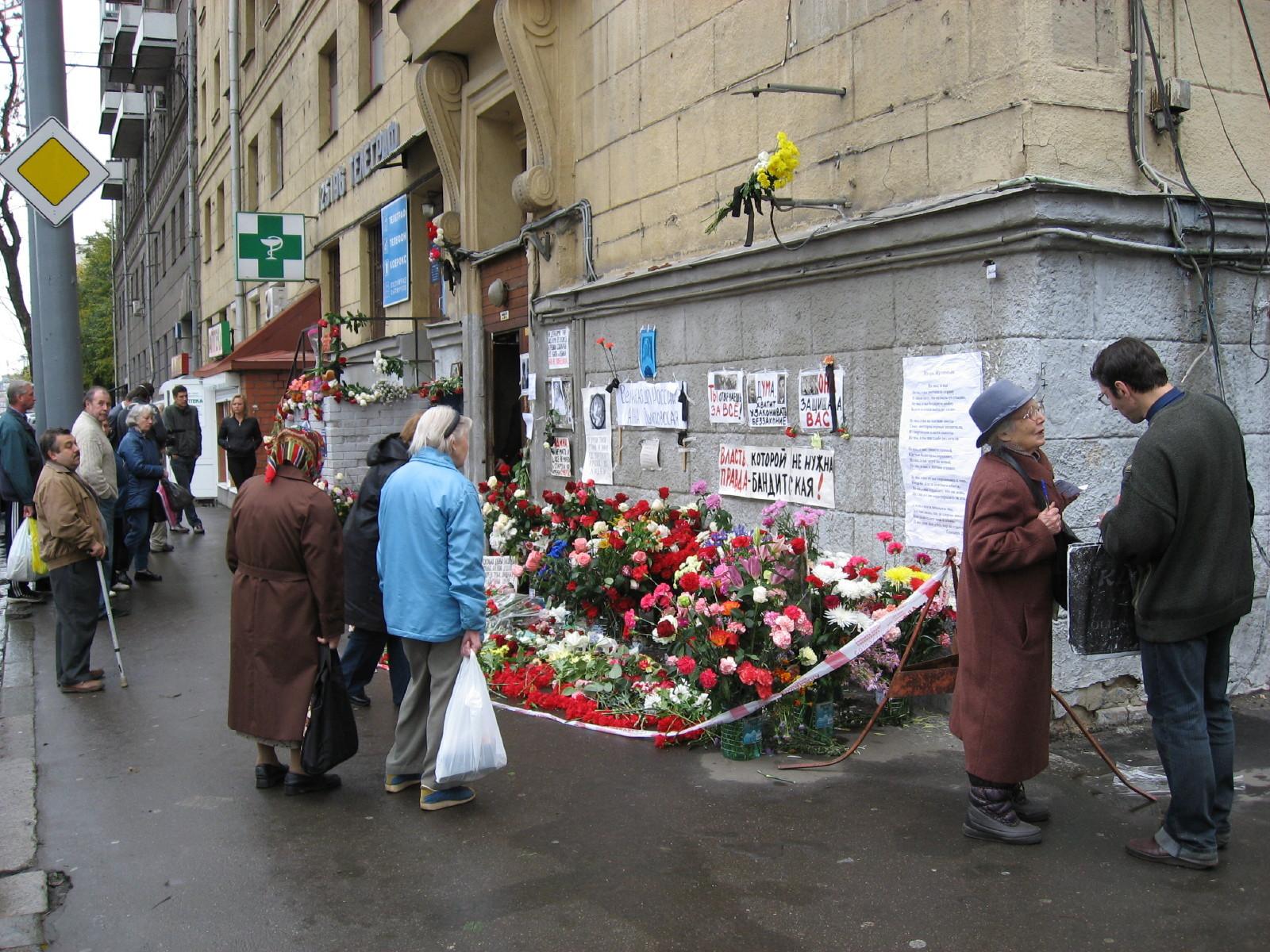Menschen legen Blumen am Haus der Journalistin Politkowskaja ab