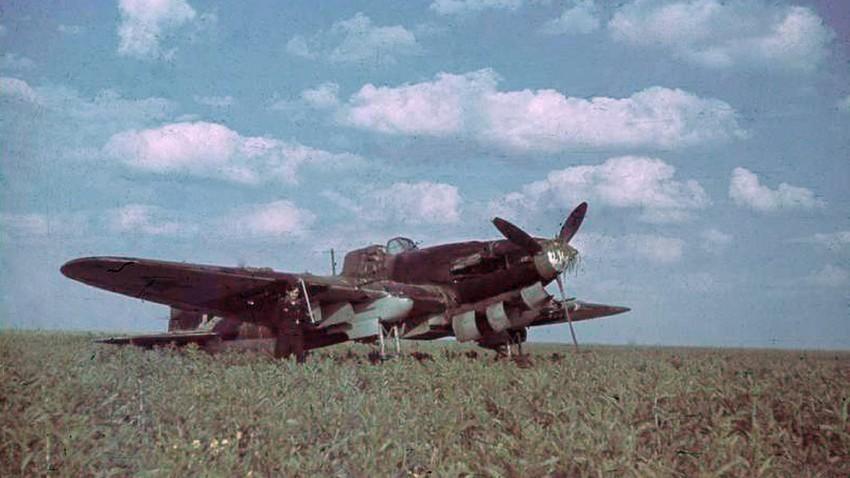 Германски войник позира до Ил-2 на поле в Русия.