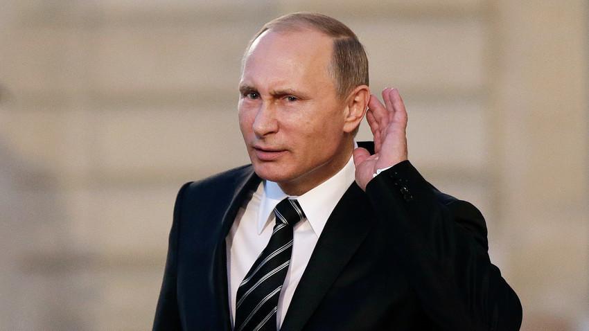 Владимир Путин надава ухо, за да чуе въпрос на тръгване от среща на върха, посветена на украинската криза в Елисейския дворец в Париж.