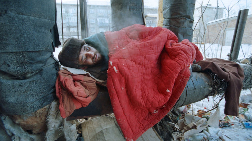 A homeless man clings to heat pipeline on a frosty day. More than 13 000 people have to survive in the streets of Moscow in extreme poverty