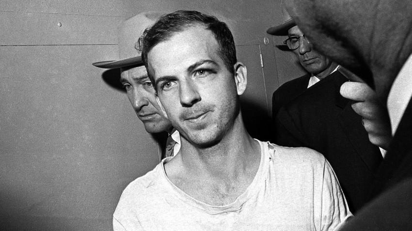 Ли Харви Освалд под придружба во ходникот на полициска станица во Далас