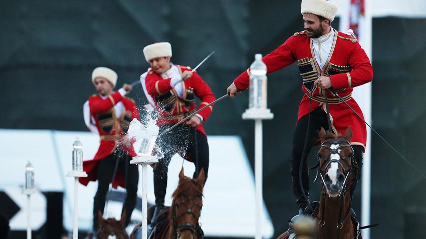 """Членове на Кавалерийния ескорт на президентския полк в Кремълското училище по езда изпълняват акробатичен номер на Червения площад на Международния фестивал за военна музика """"Спаская кула"""" през 2016 година."""