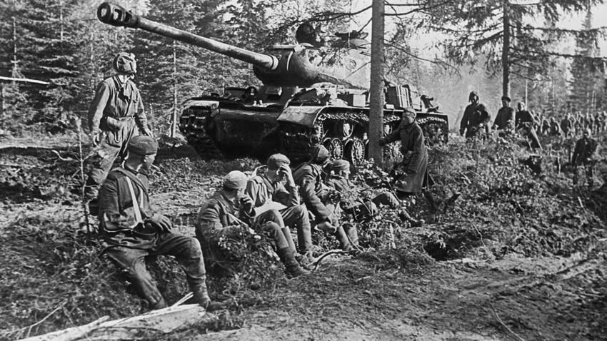 Teški tenk JS-2 i vojnici na šumskoj cesti.