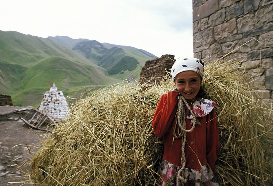 Dekle nosi slamo med žetvijo v Dagestanu (Agulski rajon, Rusija)