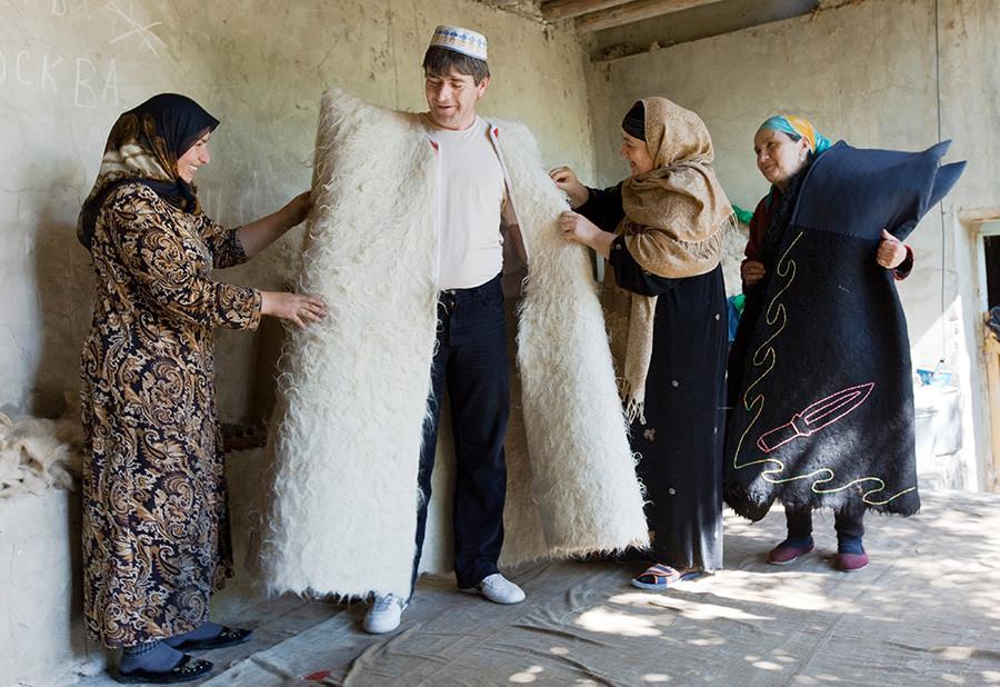 Oblačenje končane burke. Ženske iz družine Abutalipovih iz dagestanske vasi Rahata delajo burke - tradicionalna oblačila kavkaških ljudstev. Na Kavkazu danes obstaja le nekaj družin, ki se ukvarjajo s to obrtjo.