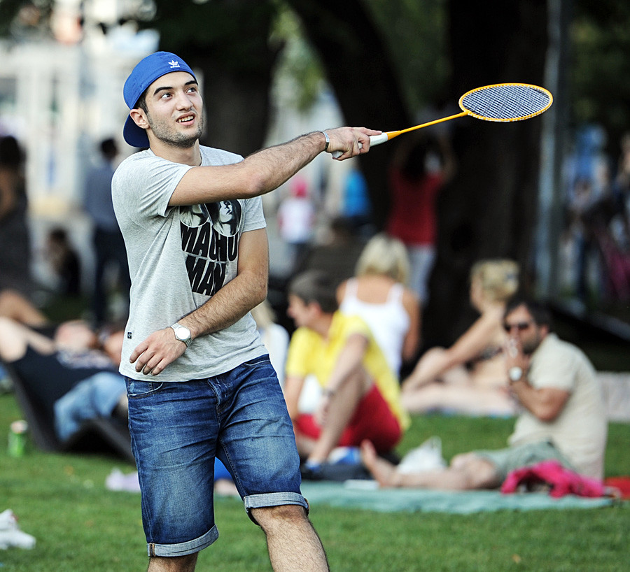 A young man enjoys badminton in a Moscow park