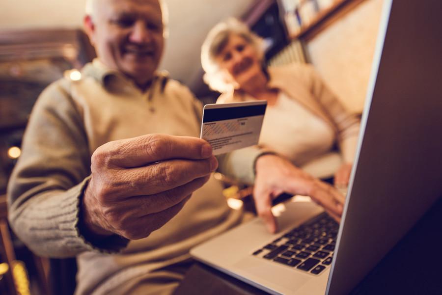 У крупном плану: старији људи плаћају нешто седећи код своје куће.