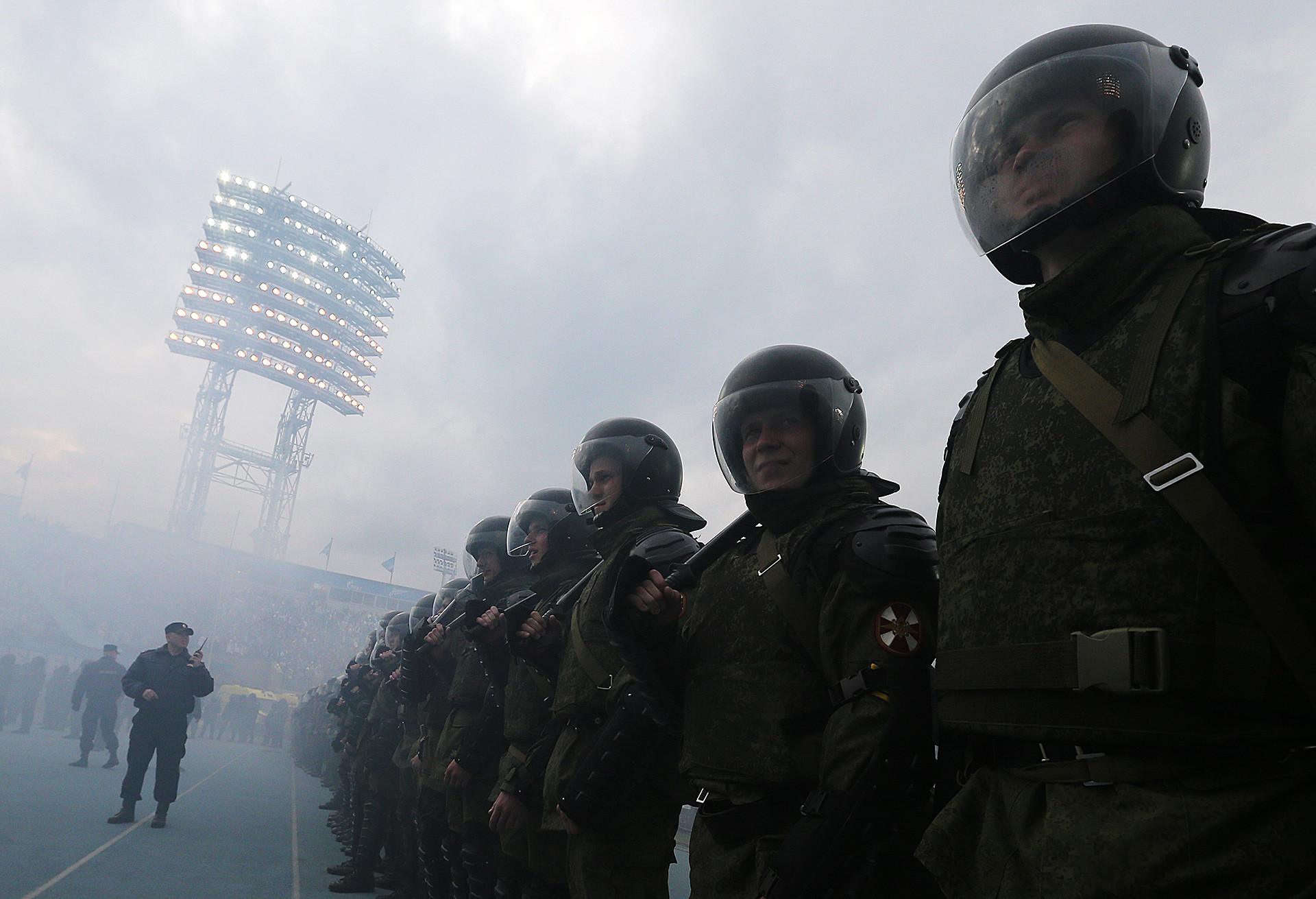 Agentes de policía observan mientras ultras lanzan bengalas durante la Liga Rusa 2014/2015.