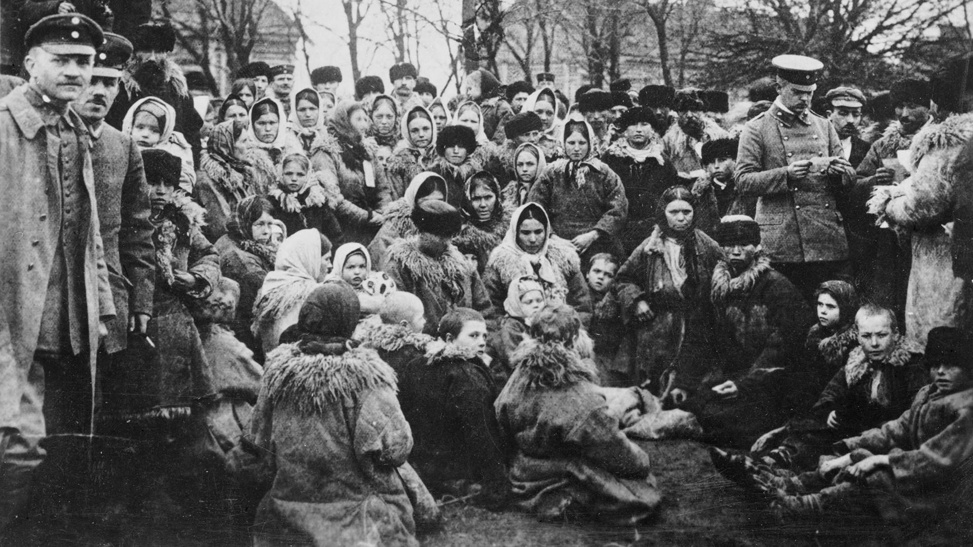 Multidão de refugiados judeus ao ar livre na Rússia. Um dos três oficiais uniformizados analisa seus documentos.