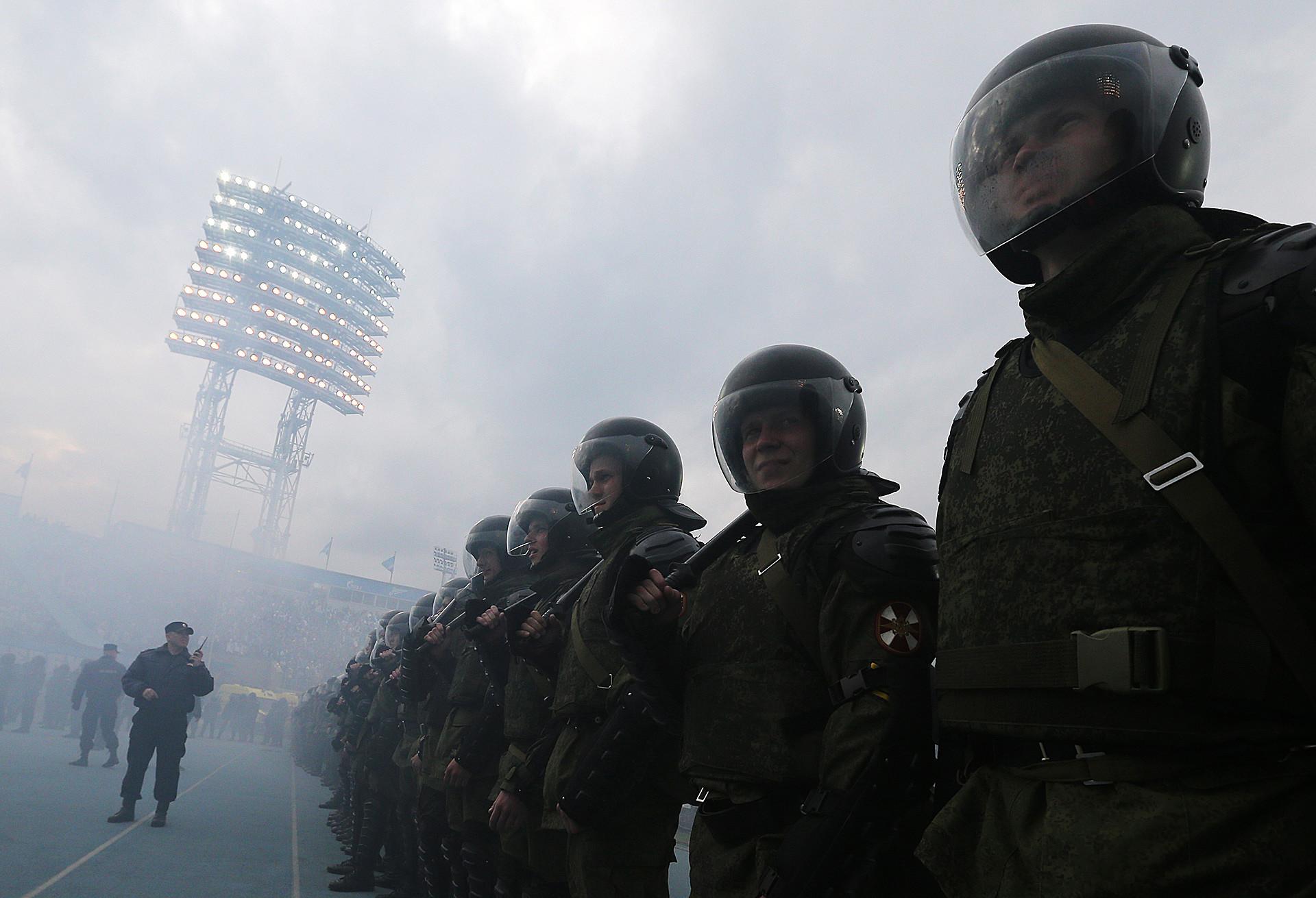 Petugas kepolisian saat penggemar sepak bola Rusia menyalakan api di Liga Primer Rusia 2014/2015.