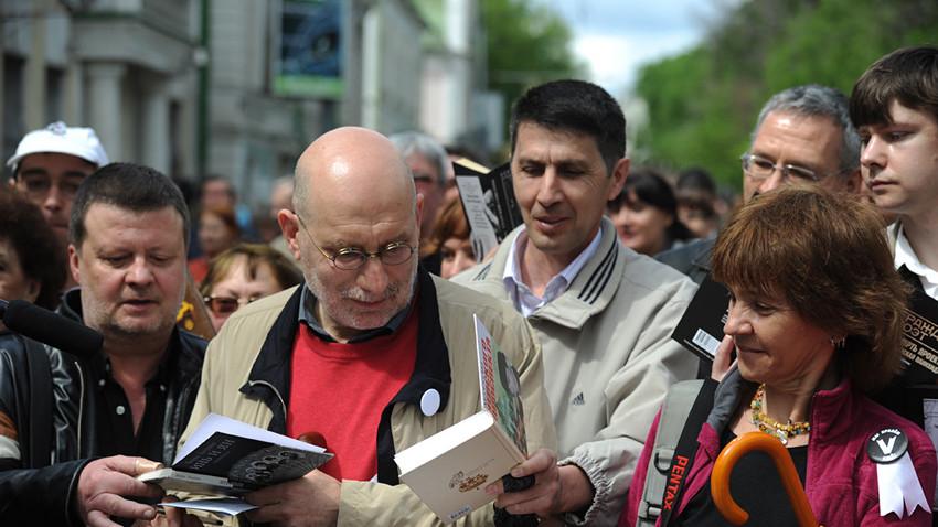 """Akúnin (de tricô vermelho) dá autografos durante a """"Marcha de Controle"""", evento da oposição organizado por escritores de renome na Rússia."""