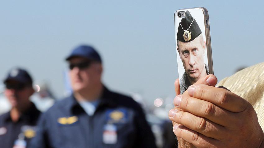 Obiskovalec fotografira letalo s telefonom, na katerem je portret Vladimirja Putina.