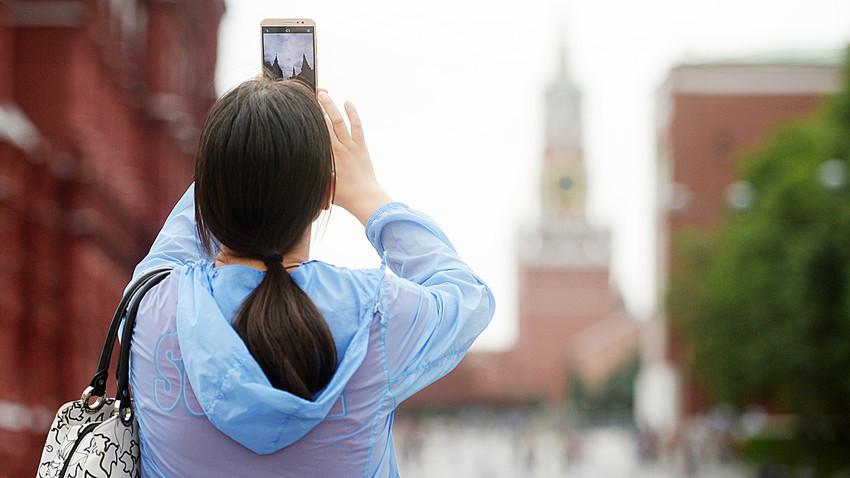 Seorang turis mengambil gambar Kremlin dengan ponselnya.