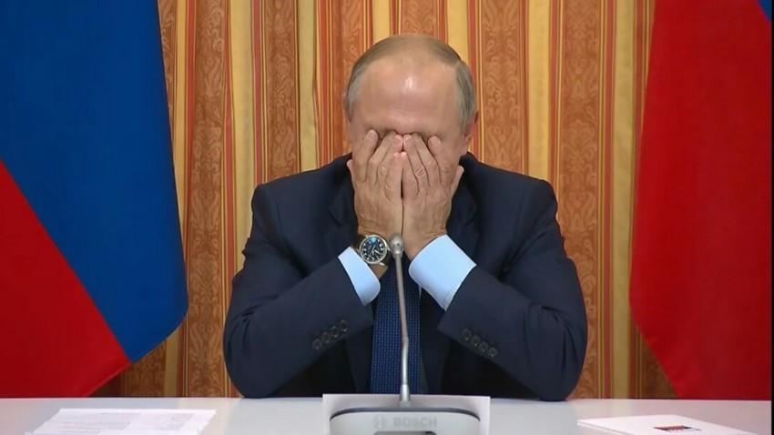 Presiden Putin spontan tertawa sambil berusaha menutup wajahnya ketika mendengar pernyataan menterinya.