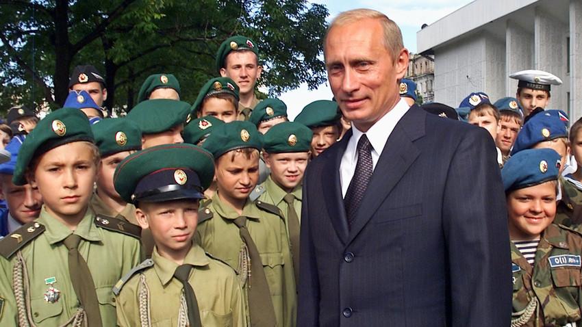 Presiden Putin berfoto dengan anak-anak berseragam militer setelah upacara persembahan ikon Fyodor Ushakov, seorang laksamana dari abad ke-18, kepada Armada Pasifik pada 2002 silam.