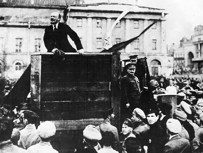 Vladimir Lenin berpidato di tengah kerumunan orang di Lapangan Sverdlov di Petrograd pada 1919. Lev Trotsky berdiri di sebelah kanannya.