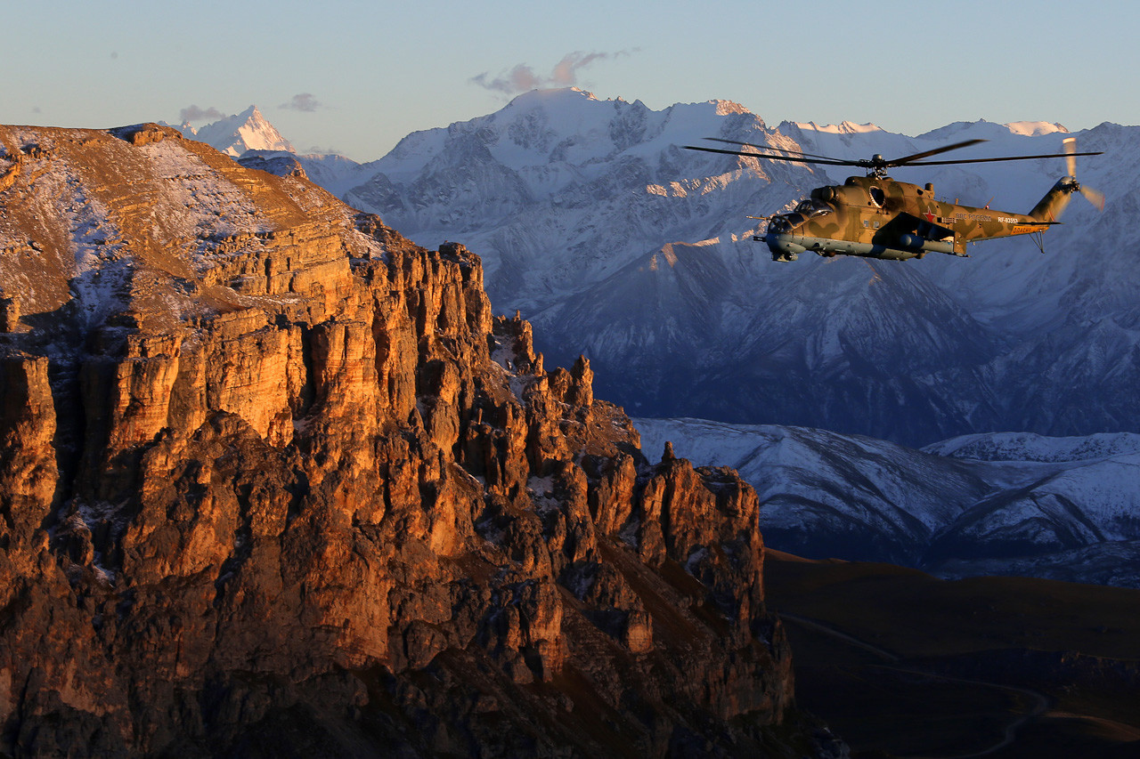 The Mi-24 helicopter, flying in the Caucasus at twilight.