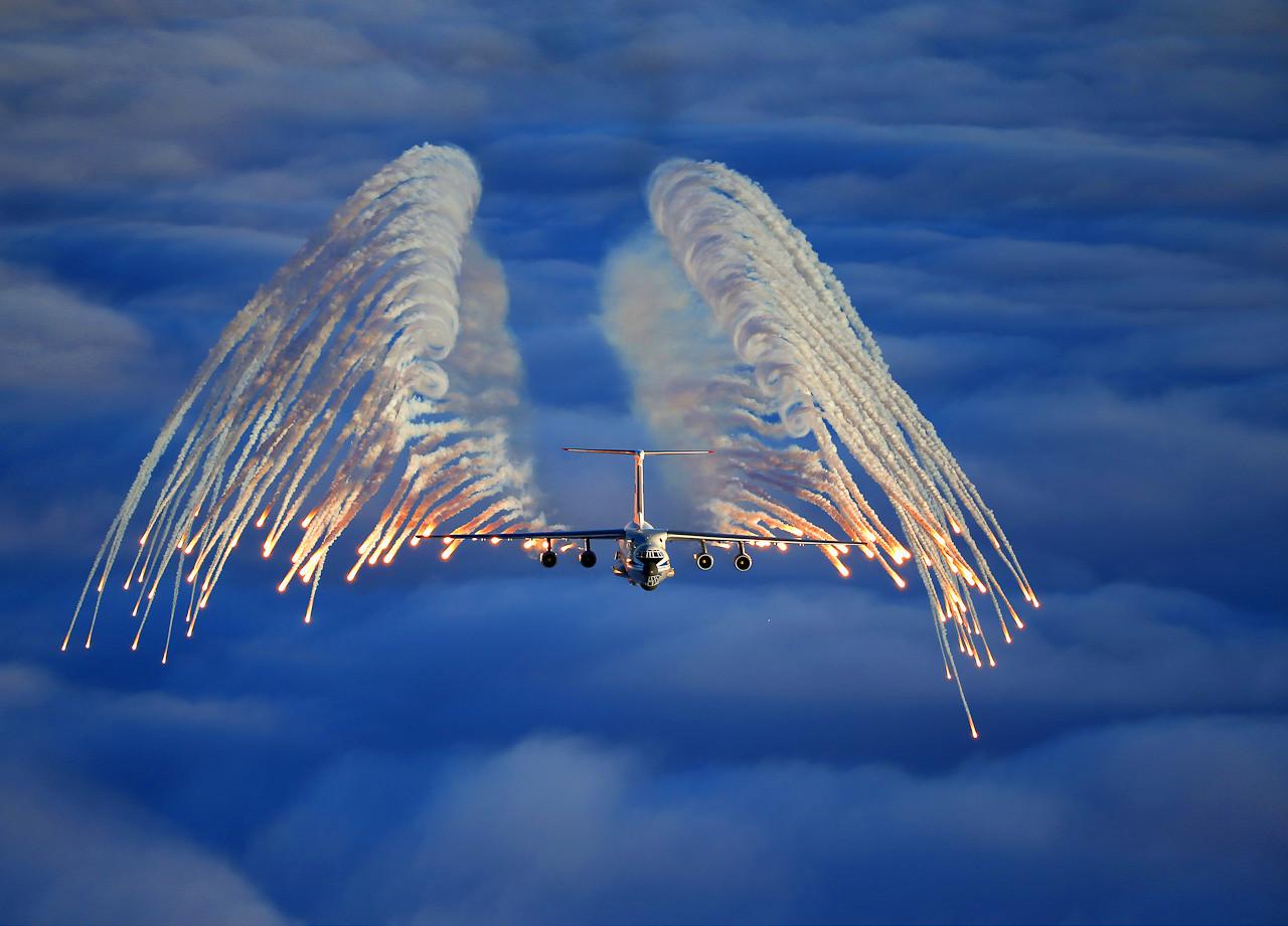 Pesawat Il-76 menyemburkan kembang api.
