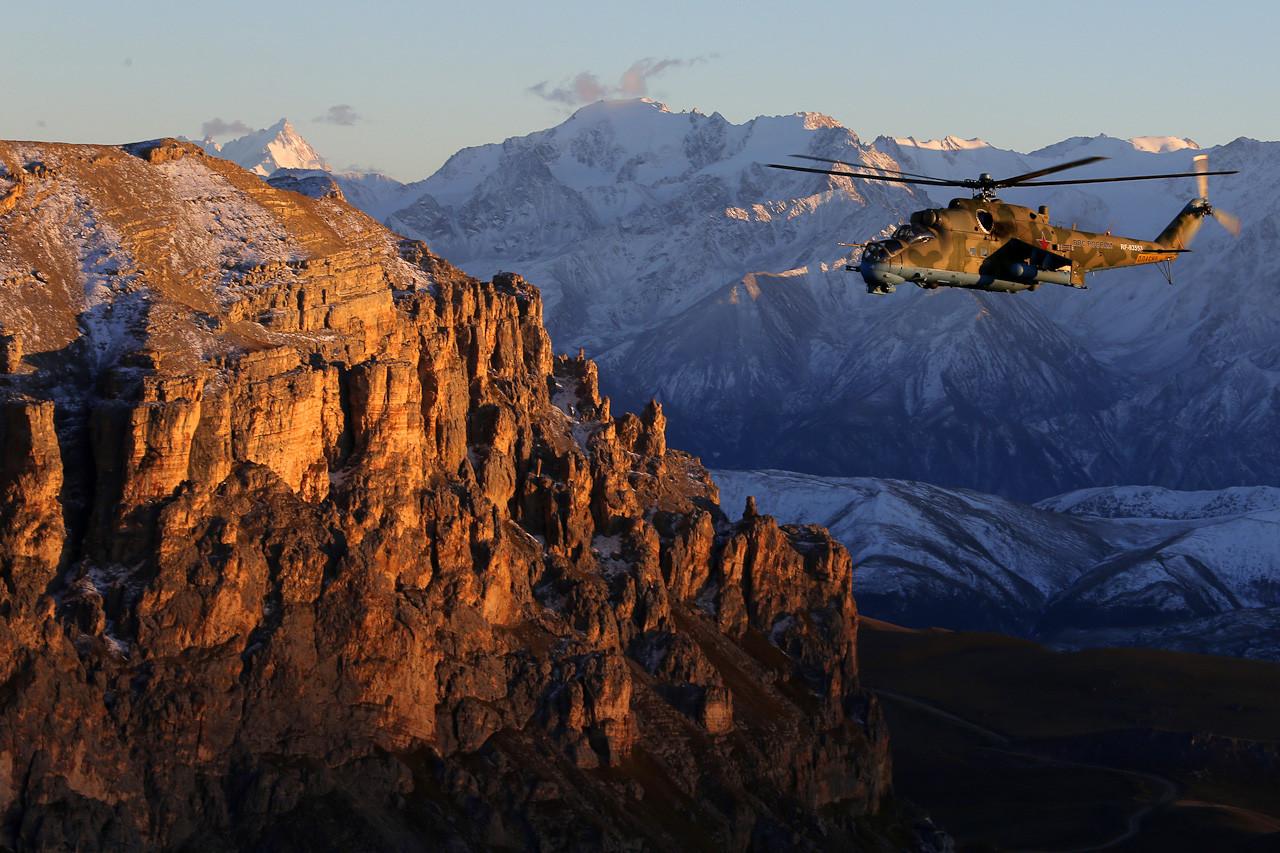 Helikopter Mi-24 terbang di langit Kaukasus pada senja hari.