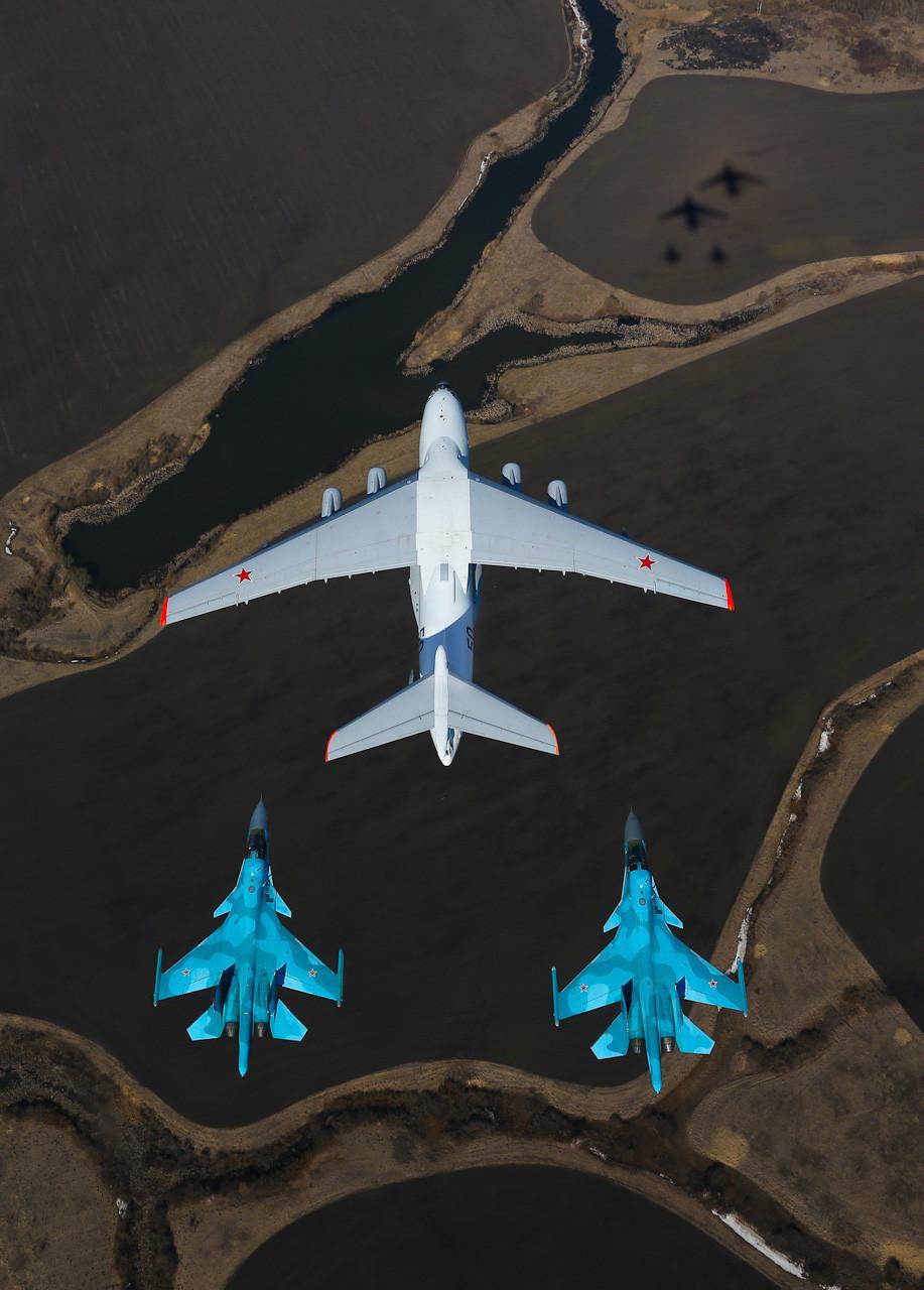 Avião para reabastecimento em voo quadrimotor Ilyushin Il-78 (baseado em seu irmão Il-76), acompanhado de dois caças-bombardeiros russos de dois assentos Su-34