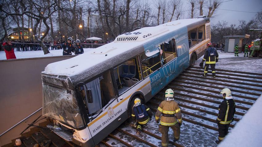 Petugas unit darurat berupaya menarik bus yang terperosok ke tangga utama menuju kereta bawah tanah Moskow, Senin (25/12).