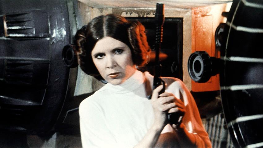 Aktris Amerika Carrie Fisher berperan sebagai Putri Leia dalam film Star Wars Episode IV: A New Hope yang ditulis, disutradarai, dan diproduksi oleh George Lucas.