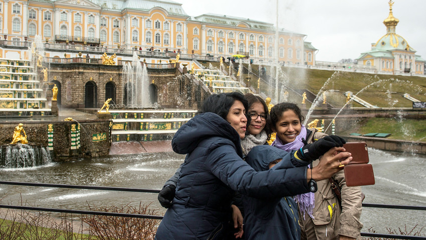 Tourists pose for photographs against the background of the Grand Cascade fountains during the opening of the summer season at the Peterhof museum-reserve.