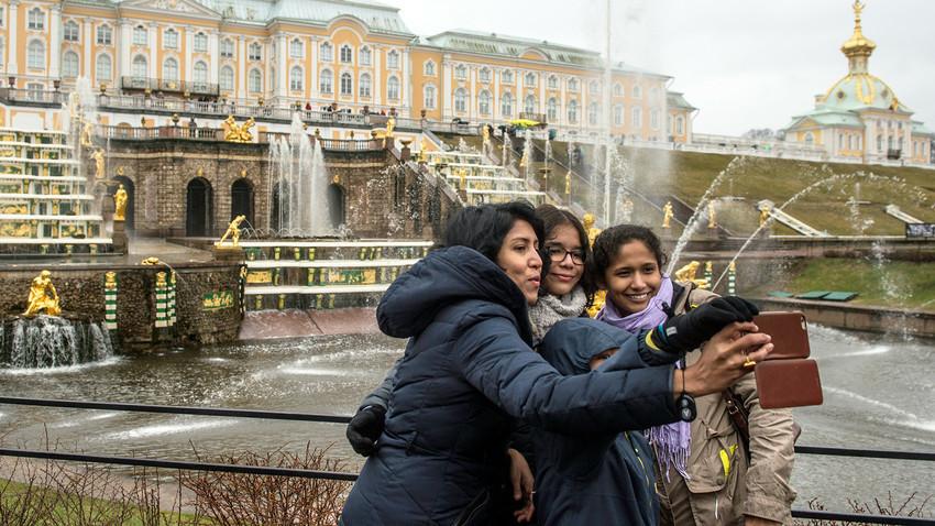 Туристи позираат пред фонтаните на Големата Каскада за време на отворањето на летната сезона во музејот-резерват Петерхоф.