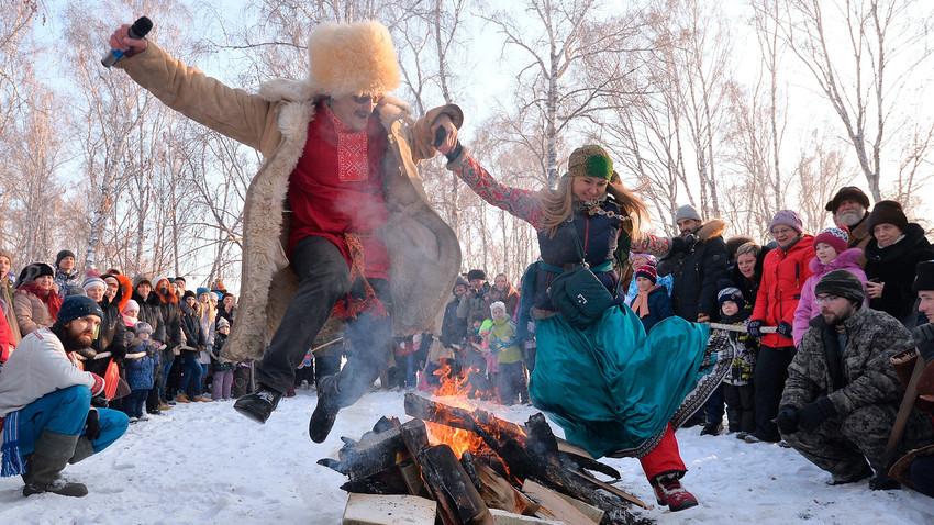 Orang-orang lompat di atas api pada Festival Svyatki 2017 di Oblast Chelyabinskaya.