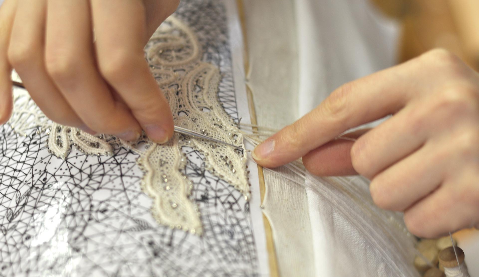 Marina sedang memembuat pola renda yang dihias dengan manik-manik.