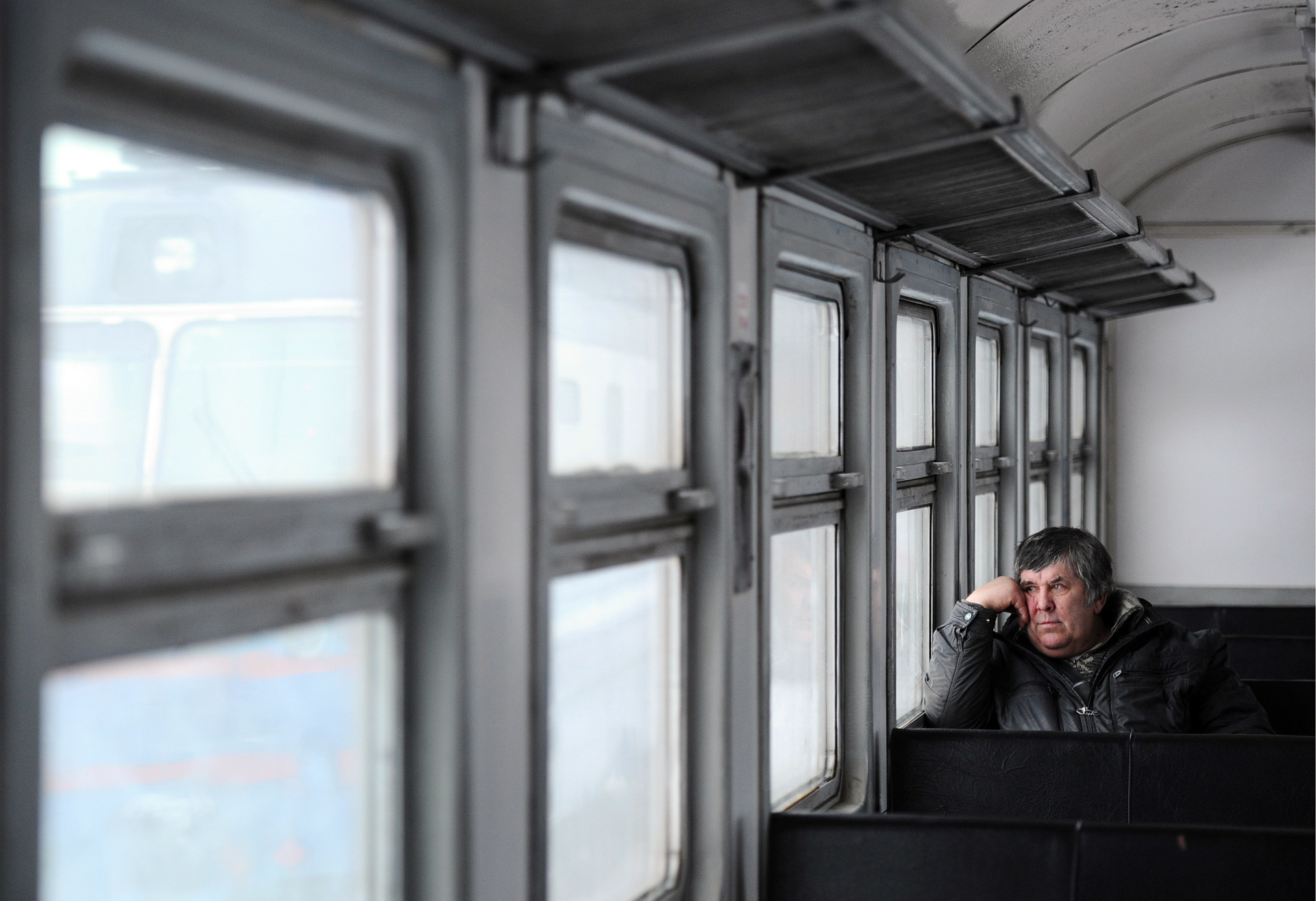 A man looks through the window as he sits in a commuter train.