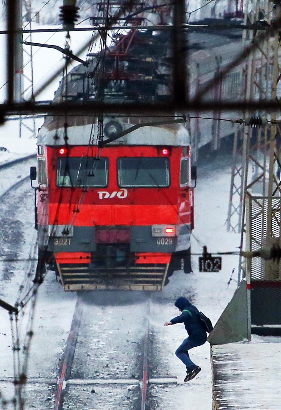 Potnik skače iz perona na eni izmed postaj.