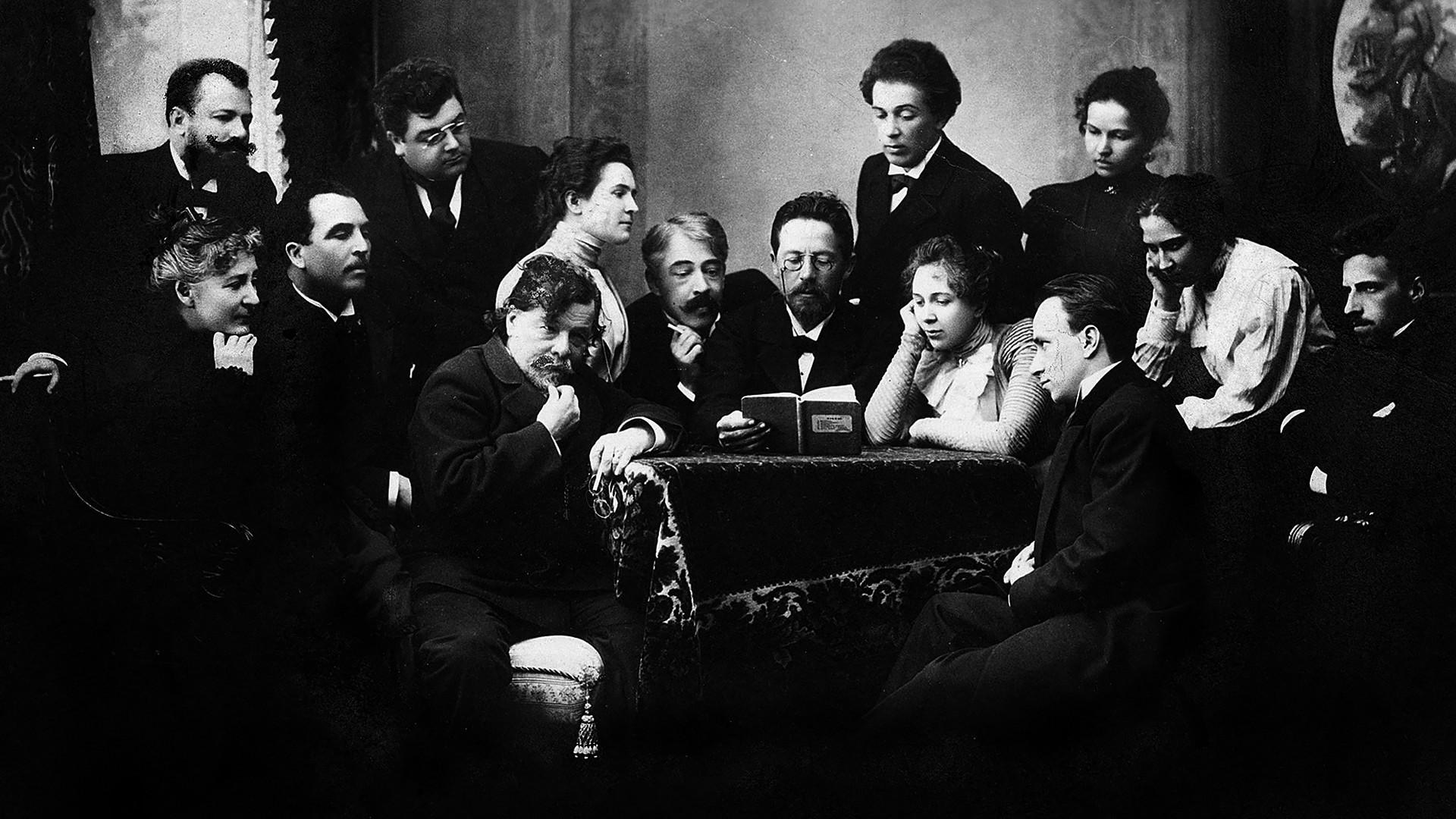 """Tchékhov lê """"A gaivota"""" a um grupo de atores do Teatro de Arte de Moscou. Entre eles estão Konstantín Stanislávski (à esq. de Tchékhov), Olga Knipper (segunda à direita de Tchékhov), Vsevolód Meyerhold (dir.), e Vladímir Nemirovitch Dantchenko (em pé à esq.)."""